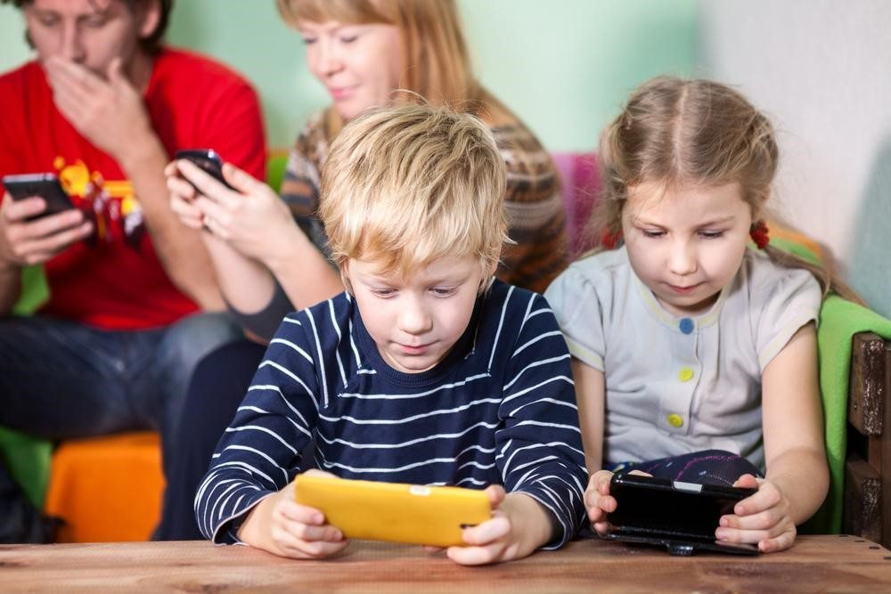 Both parents and both kids on devices